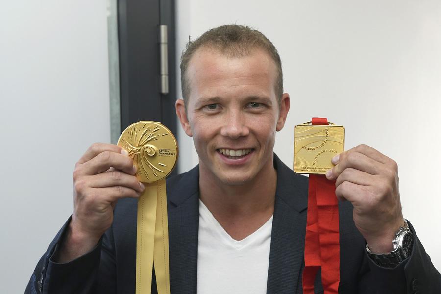 WM-Botschafter Fabian Hambüchen mit der neuen Medaille für die Turn-WM 2019 (links) und seinem Reck-Gold von 2007 in Stuttgart. | Foto: Turn-WM Stuttgart 2019